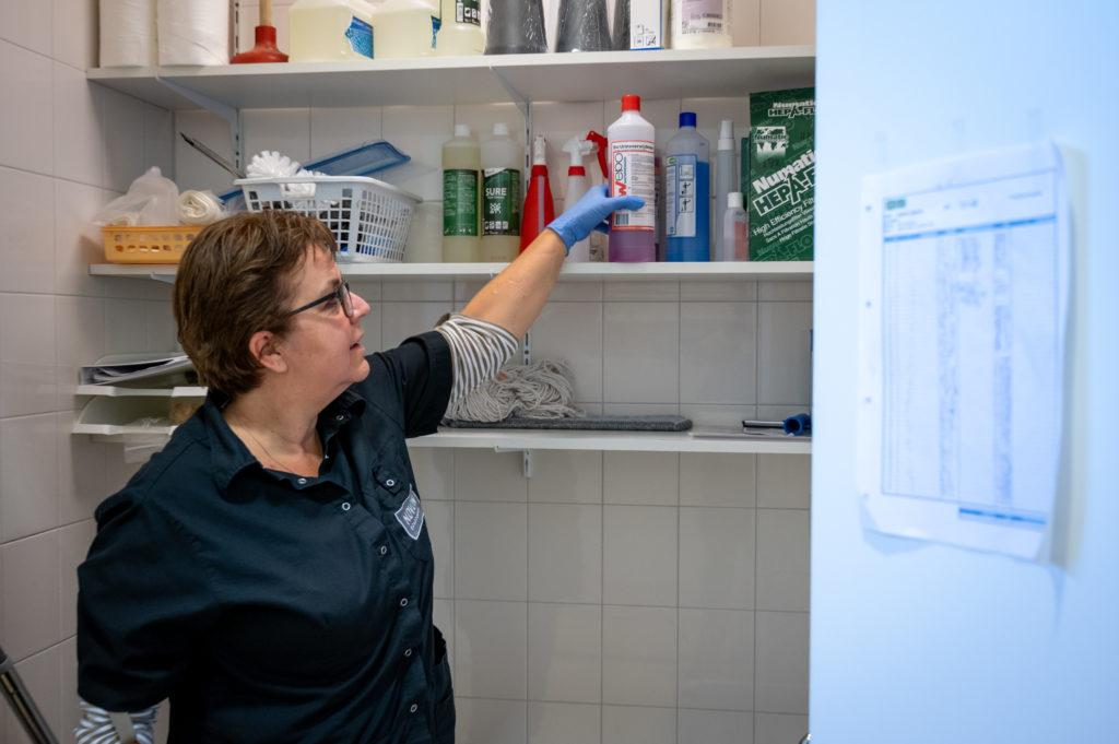 Schoonmaakster pakt een fles met schoonmaakmiddel uit een voorraadkast